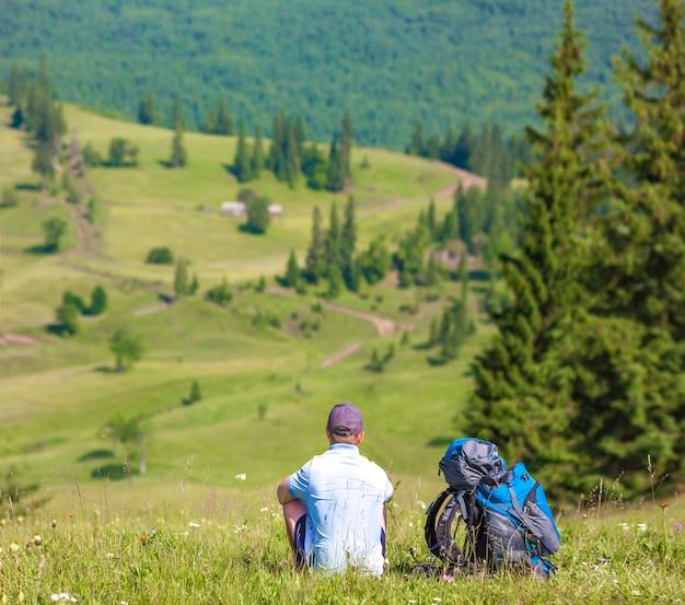 Turista solitario escursionista godendo vista montagna nella soleggiata giornata estiva