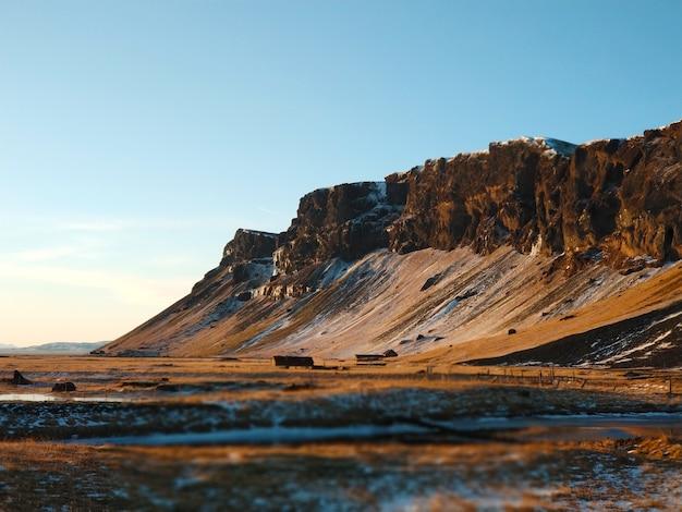 Una casa solitaria ai piedi delle montagne in islanda. incredibili paesaggi della natura