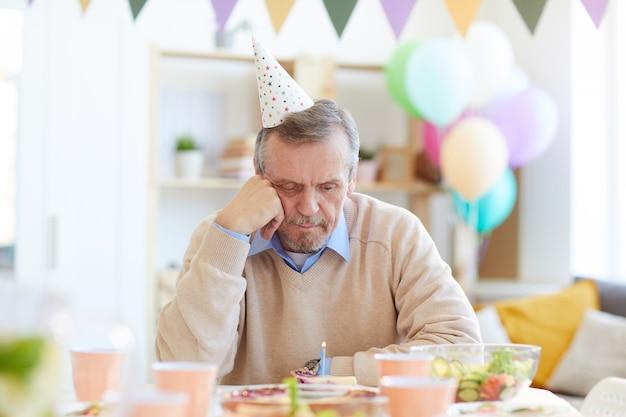 Uomo solo che esamina la torta di compleanno con la candela