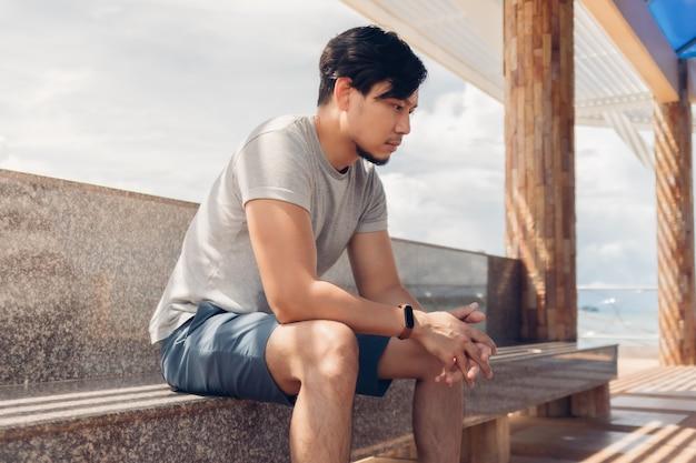 Uomo solo seduto in una capanna in riva al mare