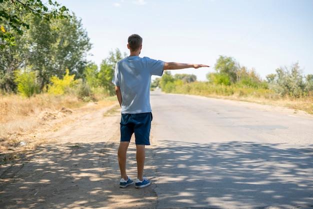 Un uomo solo in piedi sul ciglio della strada che fa un'escursione in autostop, gesto del pollice alzato in attesa dell'auto, viaggio turistico