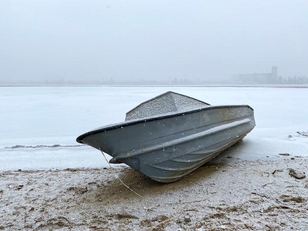 La barca da pesca a motore solitaria è parcheggiata sotto la neve sulla riva del fiume parcheggio invernale in previsione