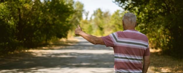 Un uomo anziano anziano solitario in piedi sul ciglio della strada che fa un'escursione in autostop, pollice sul gesto in attesa dell'auto, viaggio turistico