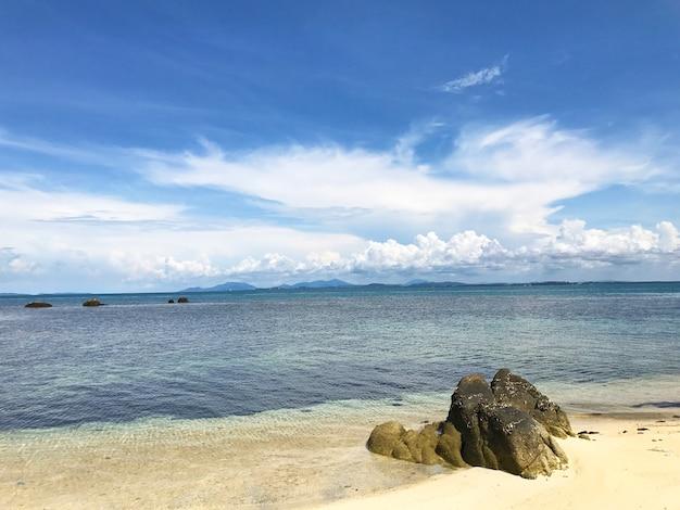 Una roccia solitaria sulla spiaggia sabbiosa con sfondo azzurro in una giornata di sole.