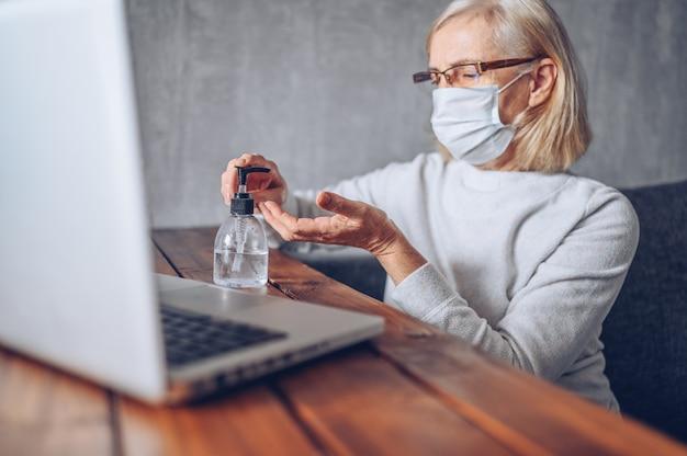 Donna senior più anziana triste sola nella maschera medica del fronte facendo uso del disinfettante liquido antibatterico della mano con la quarantena di autoisolamento del computer portatile a casa durante la pandemia del coronavirus covid19. stare a casa