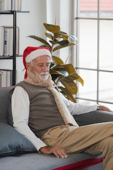 Uomo anziano solo in cappello della santa che si siede sul sofà all'interno a natale. uomo anziano triste e annoiato che pensa a casa in inverno. festeggiare da solo. vecchiaia, vacanze, problema e concetto di solitudine.