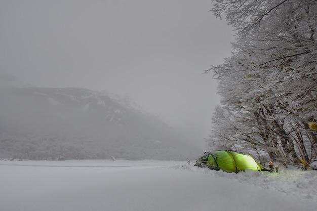 Tenda solitaria di notte con la luna piena e la neve