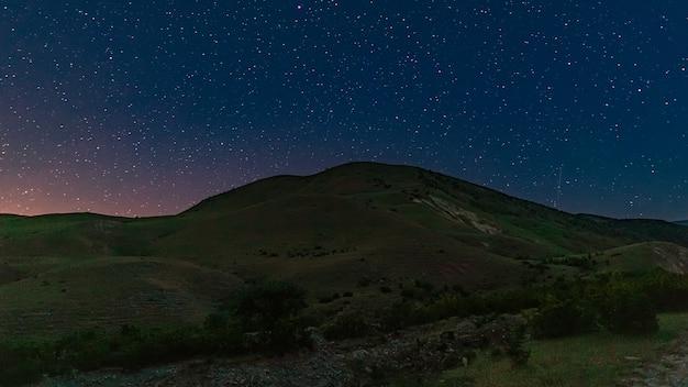 Albero solitario sul pendio della montagna di notte