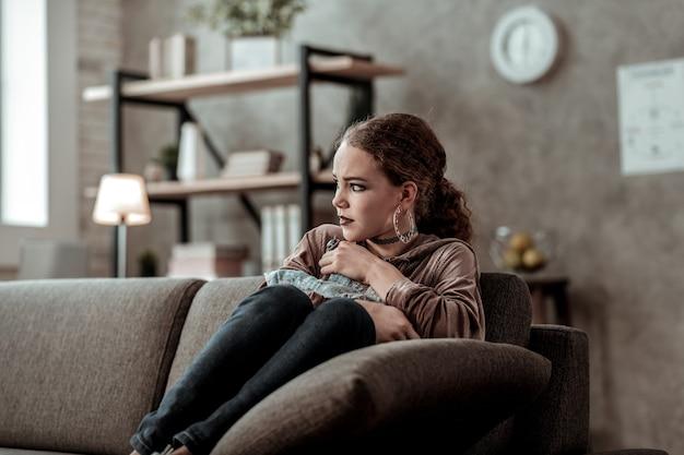 Solitario e infelice. attraente ragazza adolescente alla moda che si sente sola e infelice seduta sul divano di casa