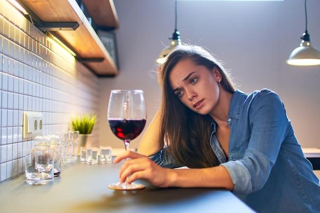 Donna bevente pensierosa stressante depressa sola sconvolta che soffre di abuso di dipendenza da alcol con bicchiere di vino rosso da solo a casa