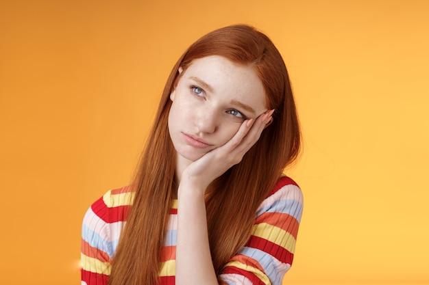 Solitario sconvolto lunatico ragazza rossa carina sensazione di noia sporgente palma guardare in alto imbronciato accigliato dispiaciuto in piedi a disagio partecipare a una riunione noiosa, fissando disinteressato riluttante sfondo arancione.