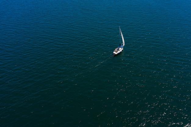 Solitario yacht a vela bianco in mare, veduta aerea, riprese con droni