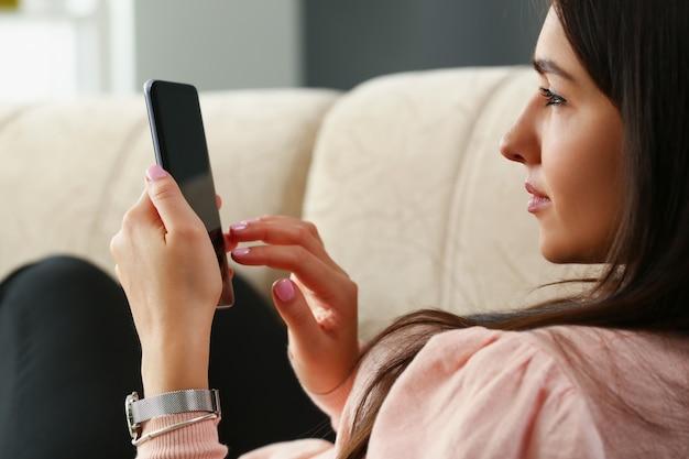 La donna sola è seduta sul divano e sta esaminando lo smartphone