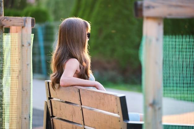 Donna sola seduta da sola sulla panchina della riva del lago in una calda serata estiva. solitudine e relax nel concetto di natura.