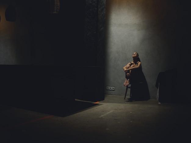 Donna sola seduta su una sedia in una stanza buia appoggiata a un muro
