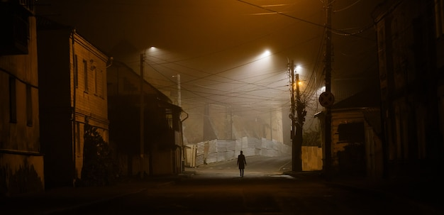 Donna sola che cammina nella città vecchia nebbiosa con lampioni in un cappotto