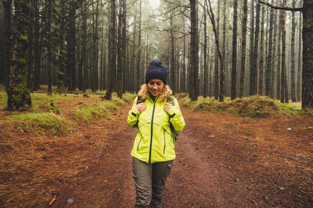 Donna sola che cammina in una foresta nebbiosa