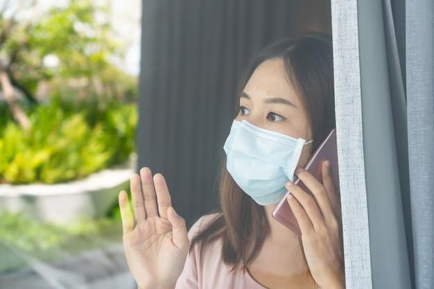 La giovane donna asiatica sola in maschera facciale zuccherina rimane isolata a casa per l'auto quarantena.