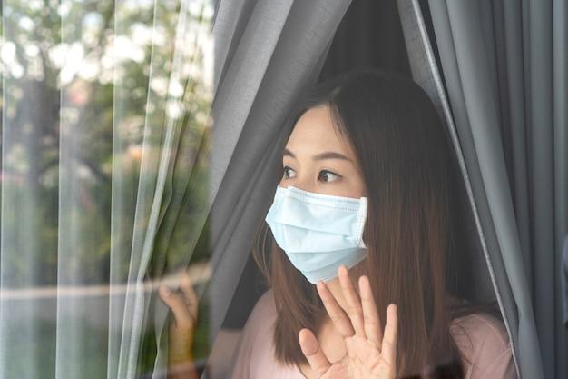 La giovane donna asiatica sola in maschera facciale zuccherina rimane isolata a casa per l'auto quarantena