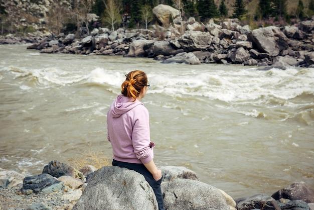 Sola giovane donna bruna di umore triste, seduta di nuovo alla telecamera su una grande pietra grigia vicino al fiume di montagna tempestoso.