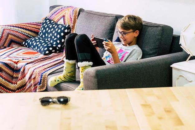 Giovani bambini caucasici soli a casa che giocano con dispositivi portatili di videogiochi tecnologici con amici connessi online