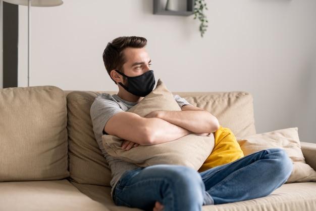 Giovane solo in maschera di stoffa seduto con cuscino sul divano e pensando alla quarantena del coronavirus