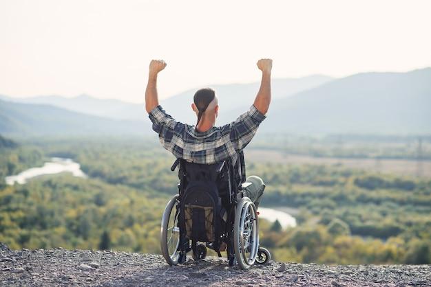 Il giovane solo in sedia a rotelle ha alzato le mani in alto gioendo della sua vittoria sulla montagna
