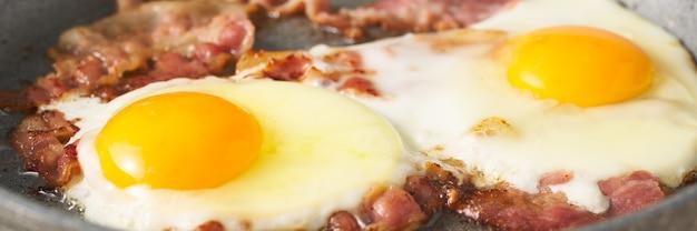 Striscione lungo con uova fritte pasto cheto con pancetta grassa due tuorlo giallo con maiale fritto