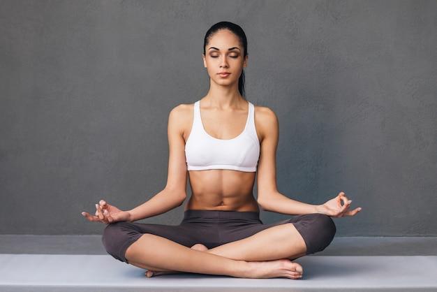 Respiro lungo. bella giovane donna africana in abbigliamento sportivo che pratica yoga mentre è seduta nella posizione del loto su sfondo grigio