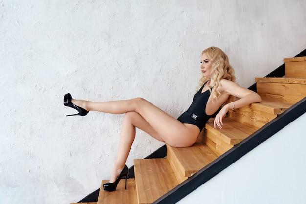 Capelli lunghi ricci donna con corpo nero e scarpe con tacchi seduti sulle scale di legno indoor