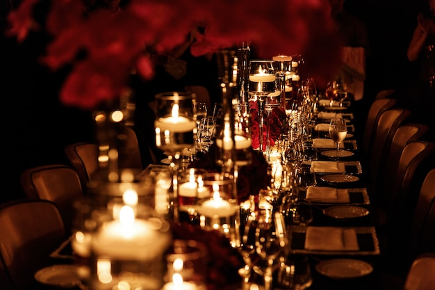 Tavolo da pranzo lungo decorato con oro, candele lucenti e fiori rossi