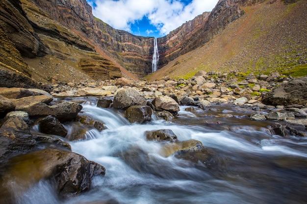 Lunga esposizione nella bellissima cascata hengifoss vista lungo il fiume. islanda
