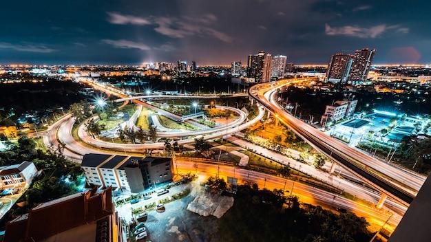Traccia di luce lunga esposizione del trasporto del traffico automobilistico sull'intersezione stradale dell'autostrada nella città di bangkok in thailandia