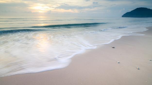 Lunga esposizione sparata spiaggia sabbiosa e le bolle bianche dell'onda del mare con lo stile dell'immagine vintage alba
