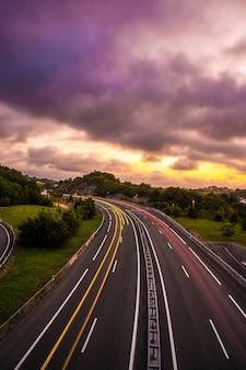 Lunga esposizione in un tramonto su una strada, entra tra le nuvole per coprire il sole e assumere un colore arancione. foto verticale, paesi baschi