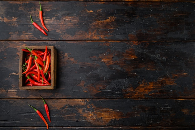 Set di peperoni a lunga alimentazione, in una scatola di legno, sul vecchio tavolo in legno scuro, vista dall'alto laici piatta