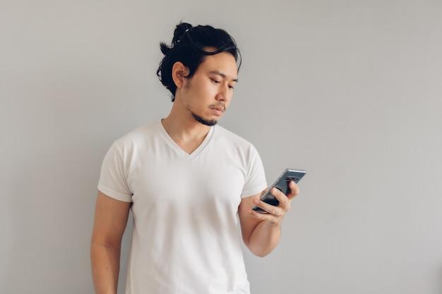 L'uomo capelli lunghi in maglietta casual bianca sta usando lo smartphone