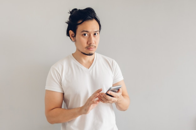 L'uomo dai capelli lunghi in maglietta casual bianca sta usando lo smartphone