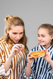 Donna adulta dai capelli lunghi che osserva il suo piccolo hamburger finto mentre la sorellina tiene in mano la versione a grandezza naturale