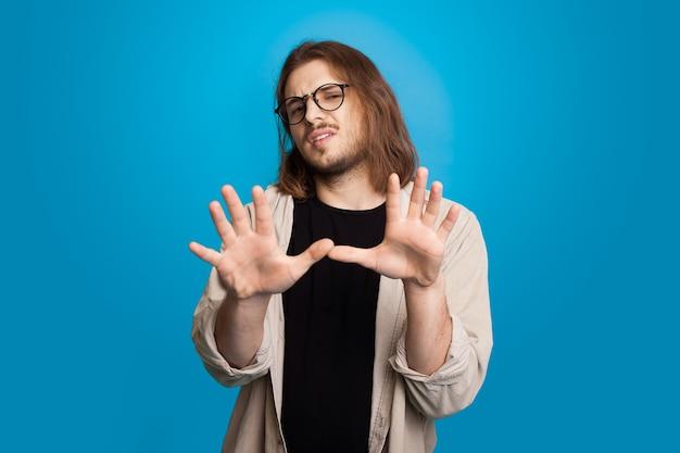 Uomo caucasico dai capelli lunghi che gesturing rifiuto con le palme con gli occhiali e la barba su una parete blu dello studio