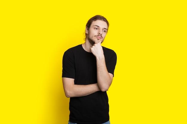 L'uomo dai capelli lunghi con la barba sta pensando a qualcosa su una parete gialla dello studio