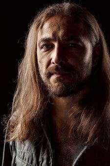 Uomo di mezza età maschile dai capelli lunghi in piedi nel buio si chiuda