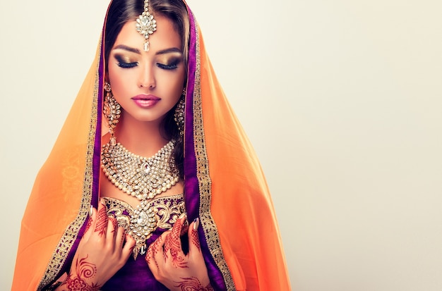 Donna orientale dai capelli lunghi con tatuaggi all'henné mehndi sulle mani