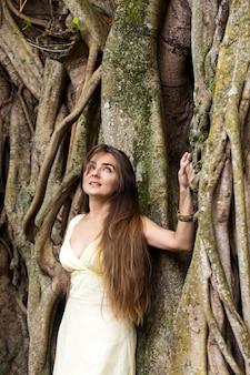 Donna dai capelli lunghi vicino a un banyan
