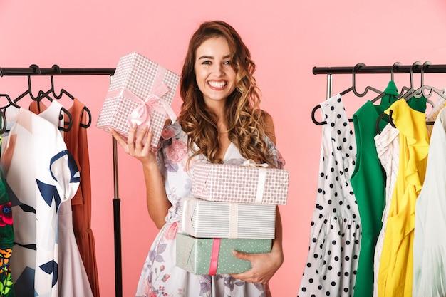 Donna con i capelli lunghi che indossa un abito in piedi in negozio vicino appendiabiti con scatole presenti isolato sul rosa