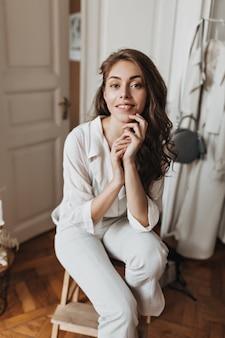 Donna dai capelli lunghi in camicia bianca che guarda l'obbiettivo e posa in appartamento