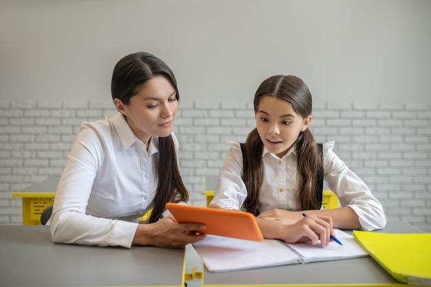 Giovane donna dai capelli lunghi che mostra tablet e studentessa sorpresa seduti insieme al banco di scuola