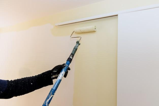 Pennello a rullo con manico lungo che applica vernice colorata sul muro con ristrutturazione della casa