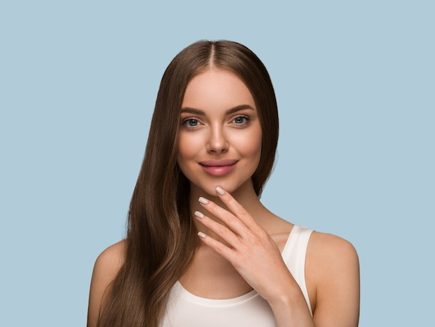 Capelli lunghi sani donna con lunghi capelli ricci bellezza pelle viso ritratto. colore di sfondo blu