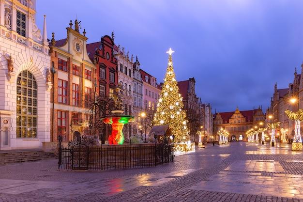 Vicolo lungo con la fontana del nettuno e l'albero di natale nella città vecchia di danzica